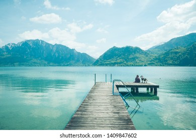 Woman with Springer Spaniel dog siting on a wooden pier at lake with beautiful mountains landscape.