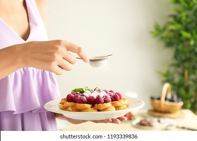 Woman sprinkling tasty homemade waffles with sugar powder, closeup