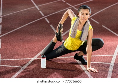 Woman sprinter doing warm up exercise before sprint in stadium