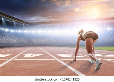 Woman sprinter start ready position on a stadium