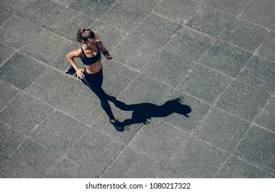 Woman sprinting in the morning outdoors. Top view of female runner working out in the city.