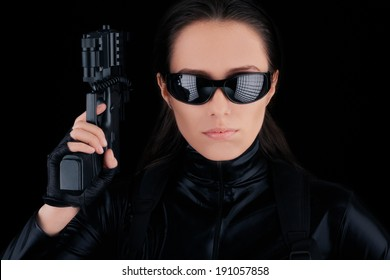 Woman Spy Holding Gun - Woman in a black leather suit holding a gun
