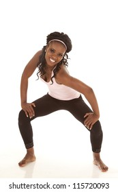 A woman in the squat position with a smile on her face.