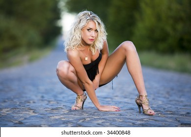 The woman squats on paved road.