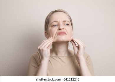A woman squeezes and pulls your skin. Are dissatisfied with their appearance, afraid of getting old. Low self-esteem, fears, neuroses, psychology of aging, gerontology, old age, middle age.