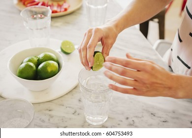 A woman squeezing fresh limes into a glass of water