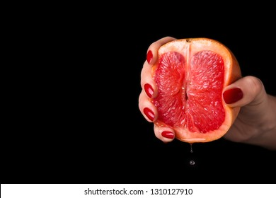 Woman squeezing half of juicy grapefruit on black background. Erotic concept