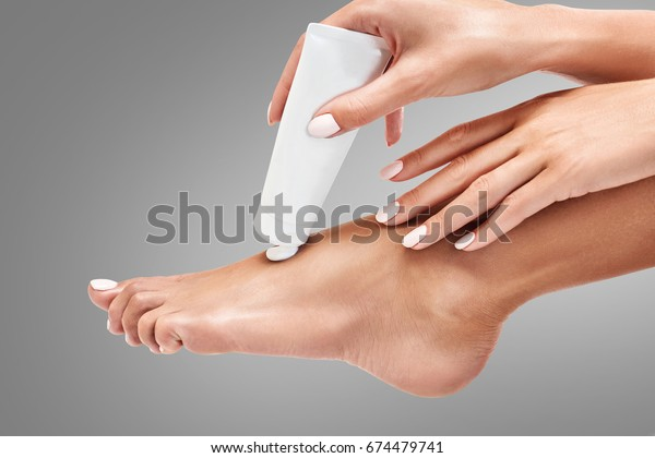 Woman squeezing moisturising cream on her leg over gray background. Healthy feet concept.