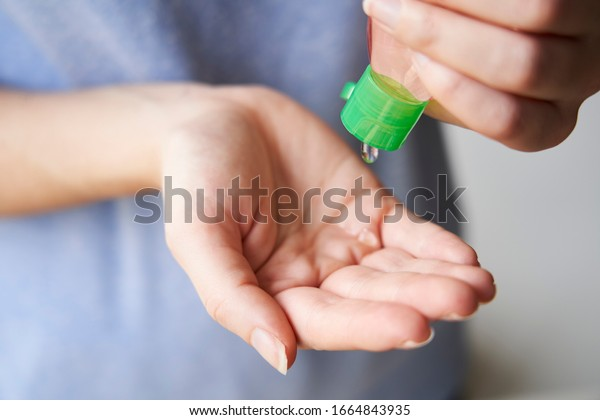 Woman squeezing sand sanitizer onto her hands from bottle