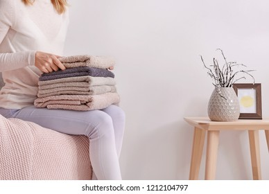 Woman with stack of clean soft towels on sofa at home