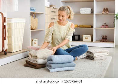 Woman with stacks of clean clothes at home