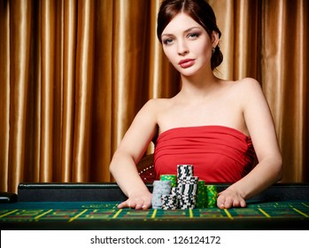 Woman stakes piles of chips playing roulette at the casino club