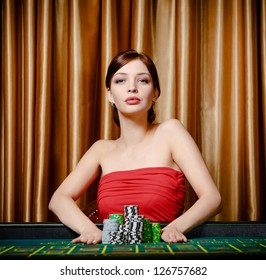 Woman stakes piles of chips playing roulette at the gambling house