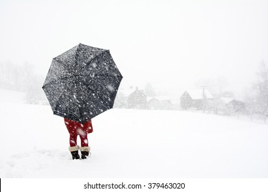 A woman stand alone in snow storm watching  falling snow in the village, Red dress woman holding black umbrella standing in snow storm, Lonely woman in the winter wonderland