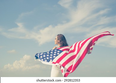 woman stand facing the sky her hands holding usa flag for freedom concept.