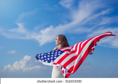woman stand facing the sky her hands holding America flag for freedom concept