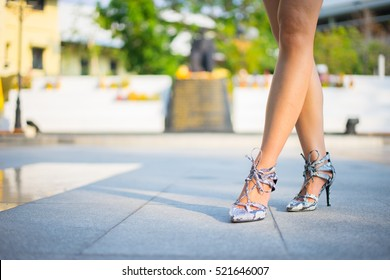 woman stand on crocodile leather high heel with shadow lie on the ground, blur, beautiful