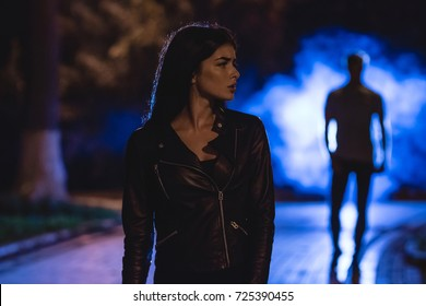 The woman stand on a dark alley on a background of the man in fume. night time