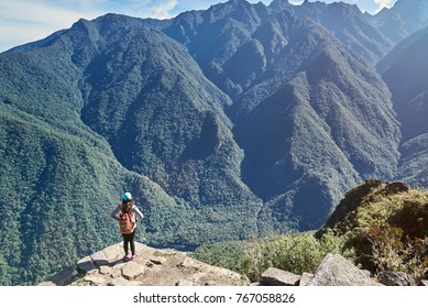 Woman stand on mountain peak above view. Young woman look on beautiful landscape