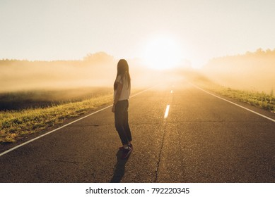 woman stand on the road with tree around, Asian traveler girl stand turn back on the road with sunshine and tree of parkland