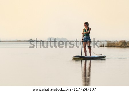 Woman stand up paddleboarding on lake. Young girl doing watersport on lake. Female tourist in swimwear during summer vacation.