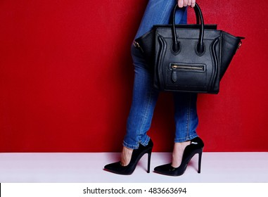 woman stand and posing in black high heel shoes and jeans with black fashion handbag. Red background studio