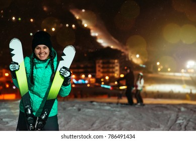 woman stand with ski on the top of the snowed hill at the evening time