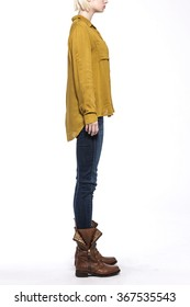 A woman stand up wearing blue denim(pants, trousers, jean) and black leather boots and indian yellow t-shirts(top) for fall back side view isolated white at the studio.