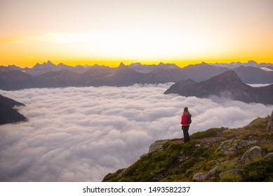 A woman standing above the clouds watching the sun rise