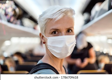 Woman standing in the airplane wearing face mask