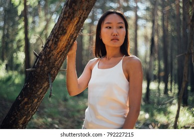Woman standing alone outdoor with wild forest on background Travel Lifestyle. Young blonde girl portrait walking in the forest. Girl in the forest.silhouette girl in the forest.