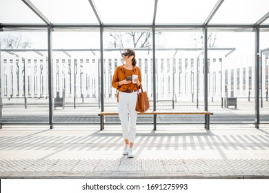 Woman standing alone at the public transport stop on a sunny day outdoors. Concept of a transportation and urban life