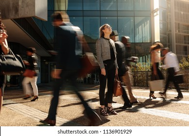 Woman standing amidst a busy office going crowd hooked to their mobile phones. Businesswoman holding her hand bag standing still on a busy street with people walking past her using mobile phones.