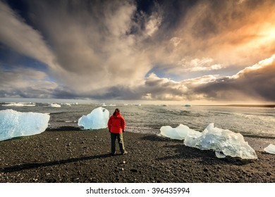 Woman standing among ice pieces on a beach in southern Iceland.
