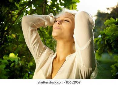 Woman standing amongst trees and relaxing.