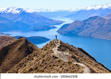 Woman standing with arms wide open at the top of the mountain watching a beautiful scenery all alone. Roy's Peak in New Zealand. Lake, snow mountains and blue sky in the background. - Shutterstock ID 1858662508