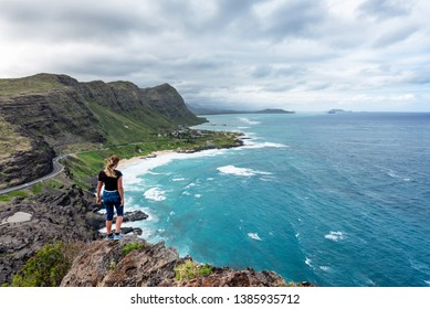 Woman standing atop a cliff overlooking Oahu, Hawaii's south shore