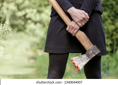 a woman is standing with an ax in a garden