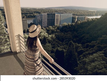Woman Standing at Balcony Looking to Distance