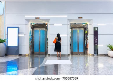 Woman standing between the elevators while waiting for elevator going up.