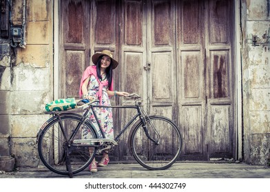 Woman standing with bicycle along the old wooden door