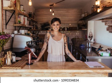 Woman standing at the billing counter of her cafe posing. Smiling restaurant owner standing beside the billing machine.