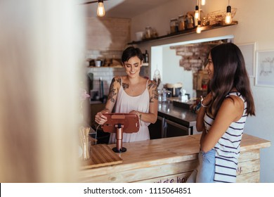 Woman standing at the billing counter of her cafe accepting orders. Woman ordering food across the counter at a restaurant.