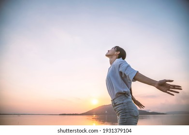 A woman standing and breathed fresh air at the river in sunset