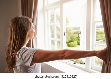 Woman Standing By Bedroom Window And Opening Curtains