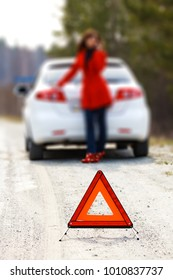 Woman standing by the broken car and warning triangle sign. Shallow depth of view.