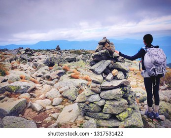 A woman standing by cairn marker and hiking on Lion Head trail in summer on Mt. Washington in the White Mountains of New Hampshire United States.