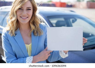Woman standing by car holding a white blank poster. Attractive blonde with a clean sheet of paper or your text.