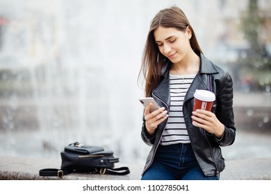 Woman standing by fountain and using her smartphone outdoors.