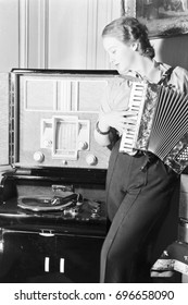 Woman standing by gramophone and playing accordion